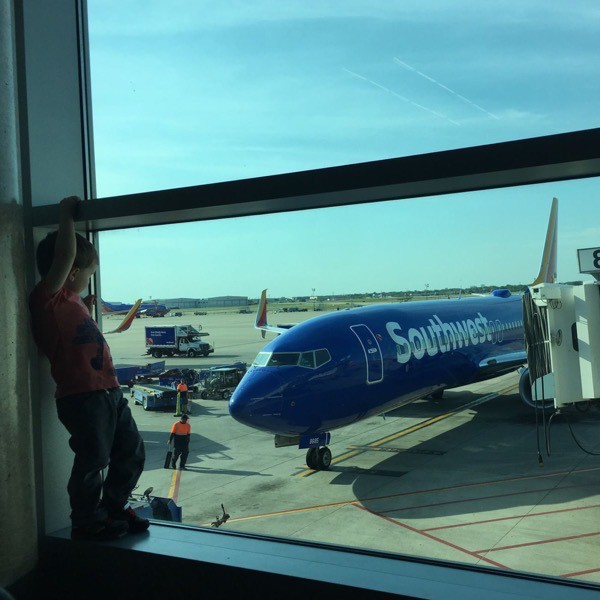 Boy stands in the window by an airplane at an airport gate