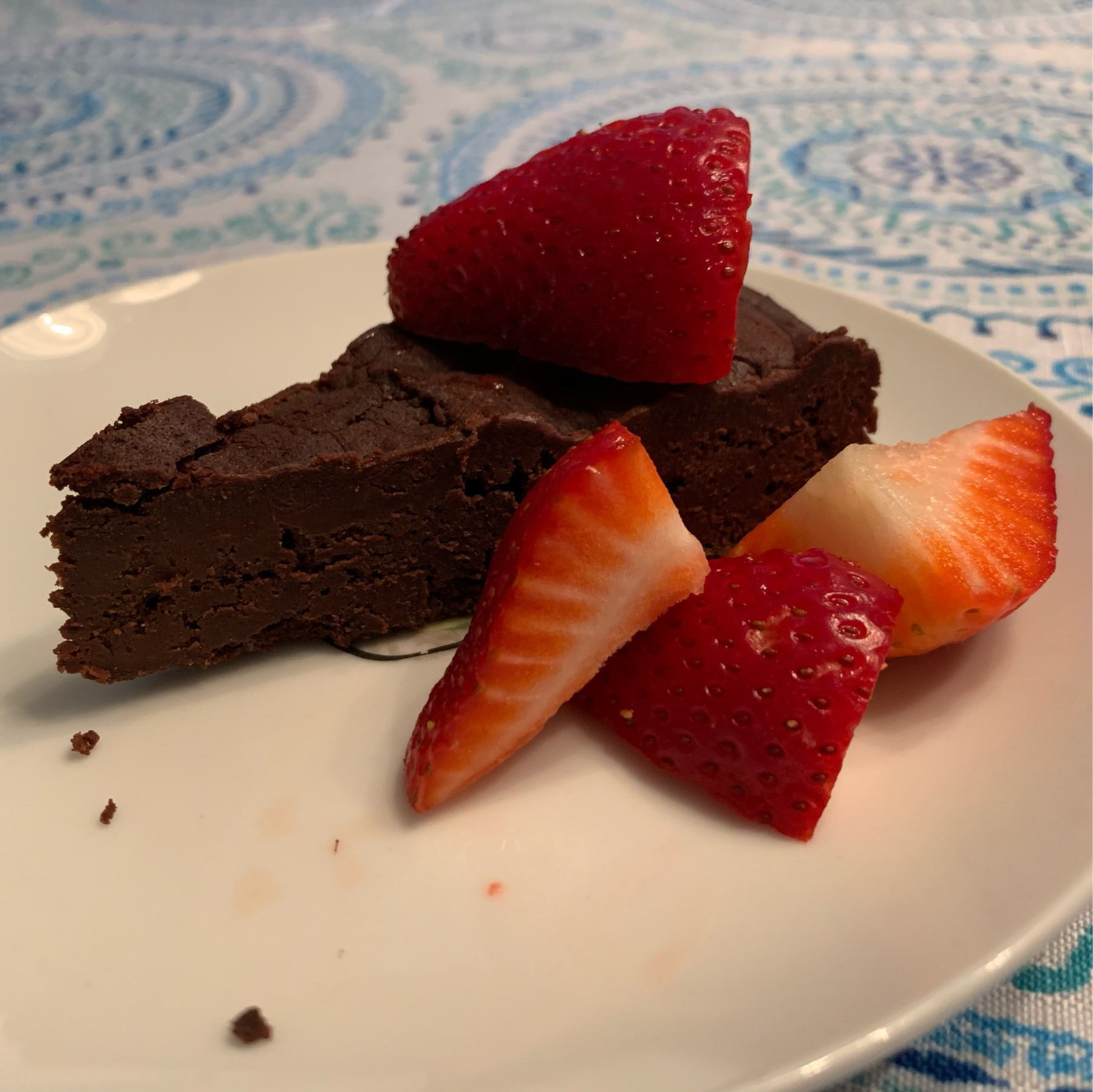 Slice of chocolate torte on a plate, garnished with strawberry quarters