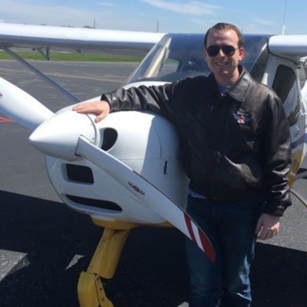 Chet standing with a Light Sport airplane