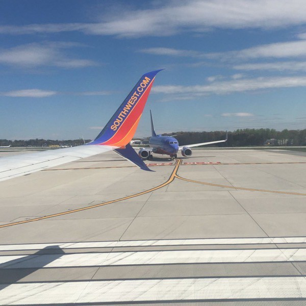 Southwest airline holds short of the runway, with a Boeing 737 wing in view