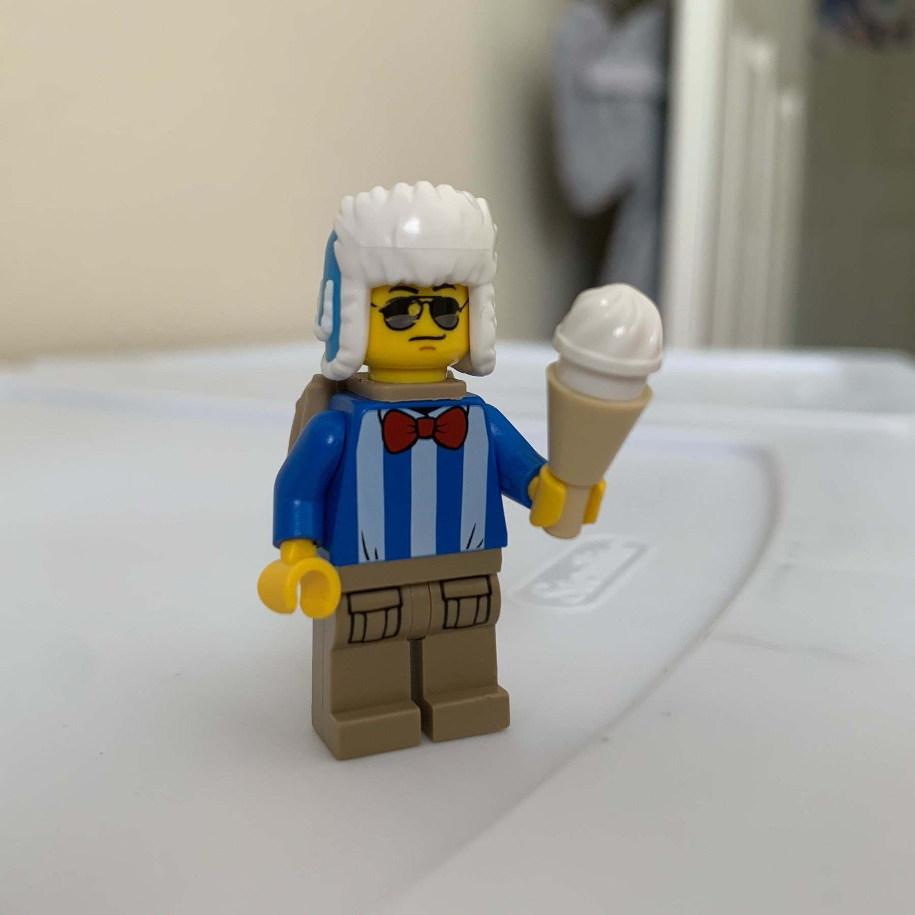 LEGO minifigure wearing blue shirt, red bowtie, sunglasses, backpack, winter hat, and holding an ice cream cone.